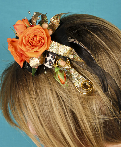 [Image: This fun orange headpiece features fun orange flowers with gold & leopard print ribbon. Such a fun added detail to any prom dress.]