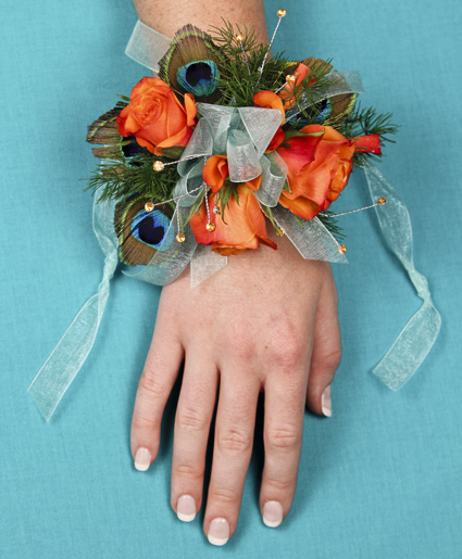 [Image: This prom corsage is great with the orange flowers and accents of peacock feathers and blue ribbon.]