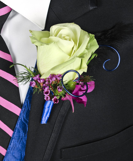 [Image: This prom boutonniere is so fun with the light green tinted rose, accents of purple flowers and the blue wire and ribbon.]