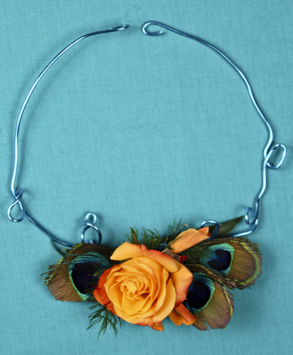 [Image: This necklace is truly fun. The feature of an orange flower with the accents of peacock feathers and blue wire makes this truly unique.]