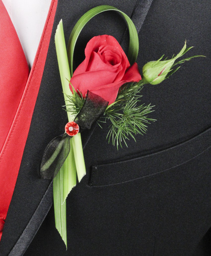 [Image: This red boutonniere features a single red rose with unique detailing of greenery.]