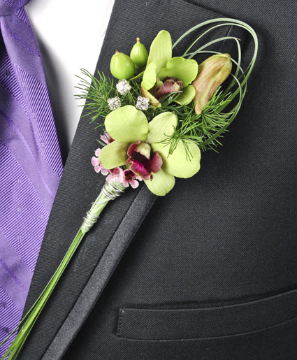 This green boutonniere features simple green flowers with unique greenery looping and crystal accents.